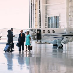 Four people in business attire in a hangar with a small jet